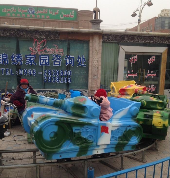 2014年、カシュガル市内にて。人民解放軍戦車のおもちゃに乗って遊ぶウイグル人の子ども(撮影:安田峰俊)